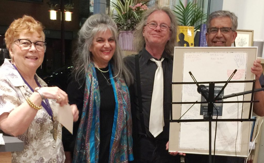 Photo of Richard Olafson and Carol Sokoloff receiving a framed tribute from some of the writers they have published over the years.