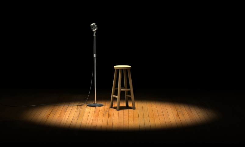 Photo of microphone and stool on an empty stage.